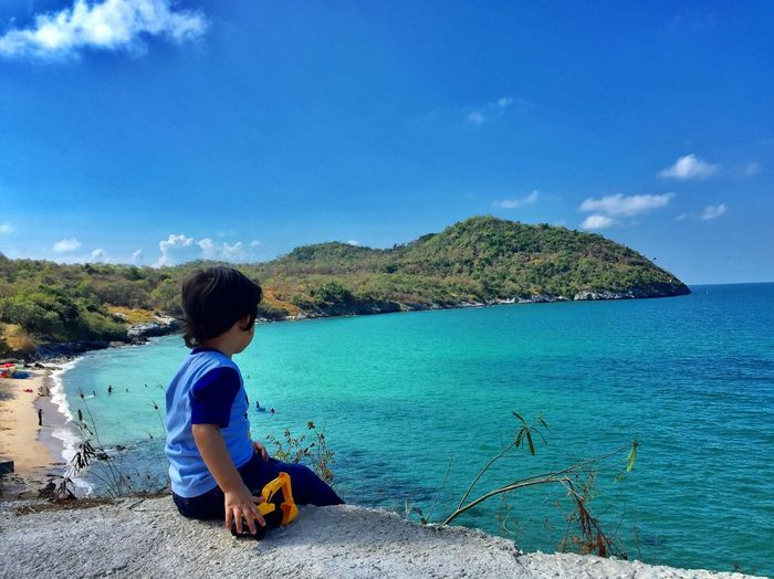 Rear View Of Boy Sitting With Toy At Beach Against Mountain And Sky