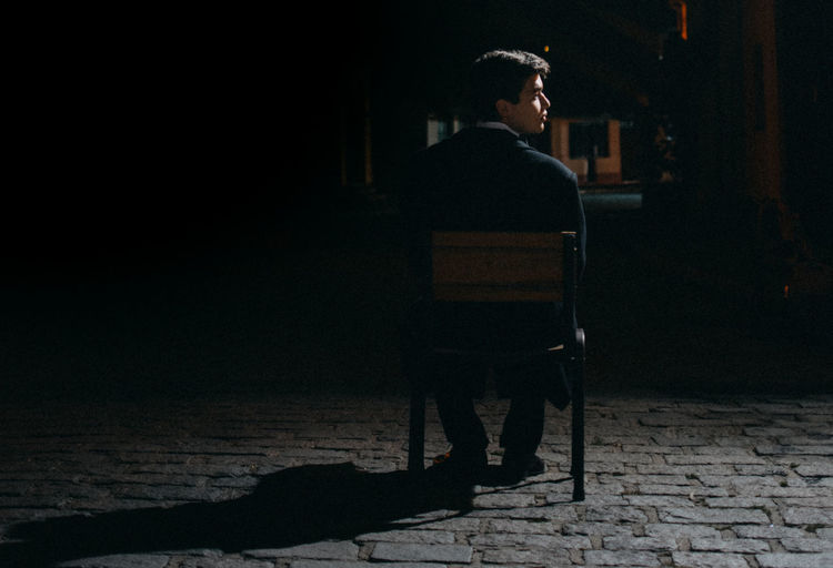 young man sitting on a chair in a street Architecture City Contemplation Dark Full Length Individuality Leisure Activity Lifestyles Looking Looking Away Modern Night Nightlife One Person Outdoors Real People Solitude Standing Young Adult Young Men