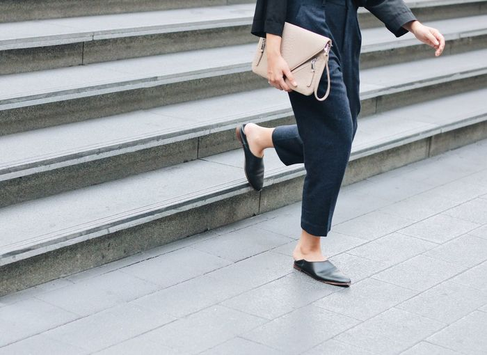 Low Section Of Woman Holding Purse While Moving Down On Steps