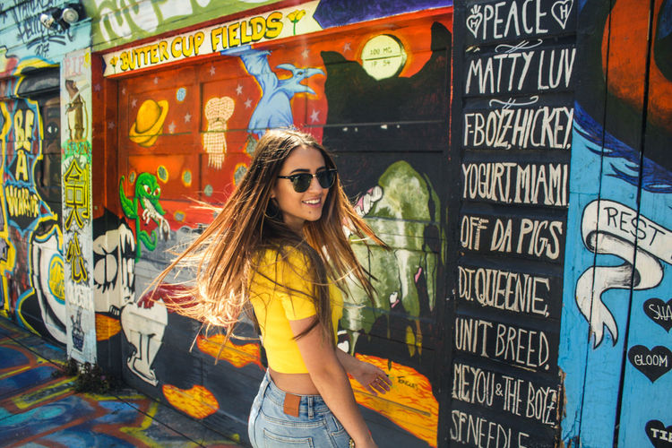 Portrait of smiling young woman standing against graffiti in city