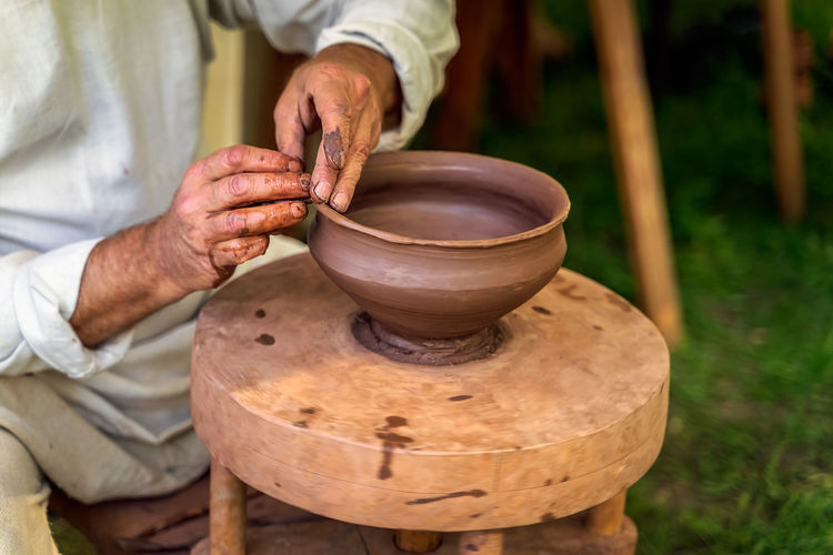 Midsection of man molding shape of pot on potters wheel