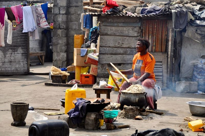 Cooking A Meal Ghana Laundry Adult Africa Corrugated Iron Hut Corrugated Roof Developing Country Hominy Hut Laundry Line Messy One Person Outdoors Poor People  Poverty Preparing Food Real People Shacks Sitting Social Issue Tropical Heat Women Working