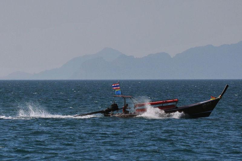 Fisherman sailing longtail boat at sea against sky