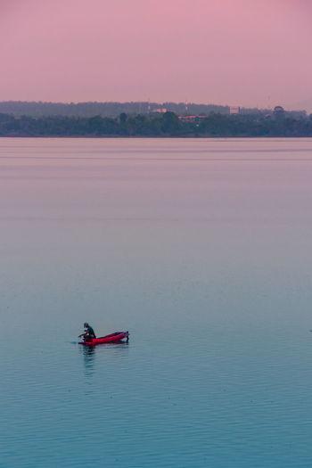 Man in canoe on lake against sky