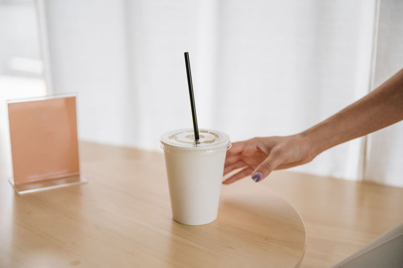 Midsection of man holding glass of table