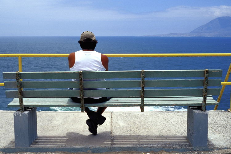 Rear View Of Man Sitting On Bench At Beach Against Sky