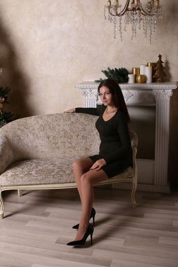 Portrait of young woman sitting on sofa against wall at home