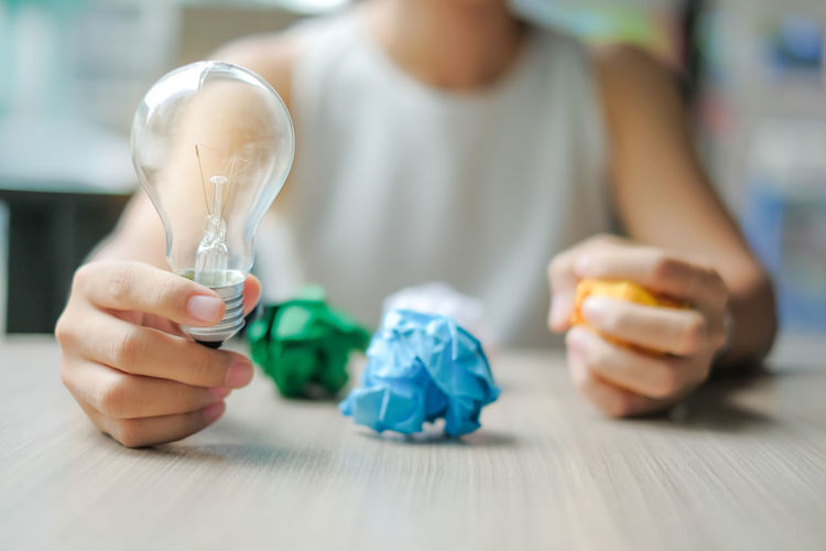 light bulb. New Idea, Creative, Genius and Innovation concepts Adult Casual Clothing Child Childhood Close-up Day Focus On Foreground Front View Hand Holding Human Body Part Human Hand Indoors  Men Midsection One Person Selective Focus Table