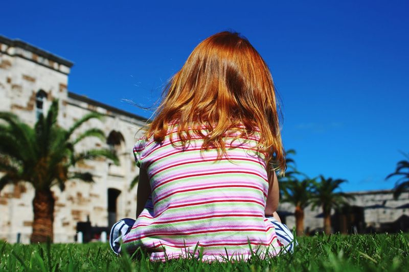 Rear view of girl sitting on grass against blue sky