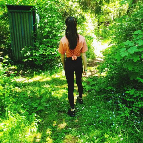Full length rear view of young woman standing amidst plants