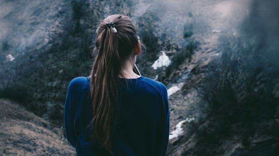 Rear view of young woman standing on mountain