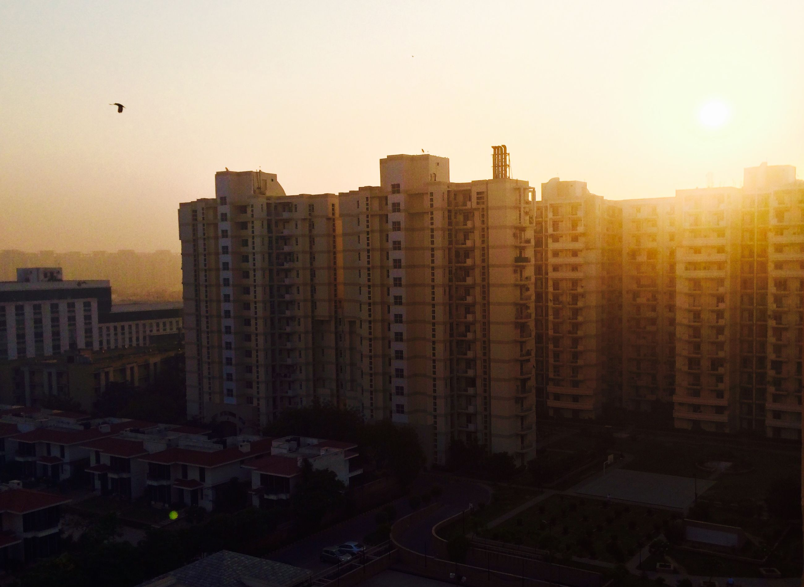 building exterior, architecture, built structure, city, clear sky, sunset, building, sunlight, sun, cityscape, skyscraper, residential building, sky, office building, modern, city life, residential structure, outdoors, residential district, tower