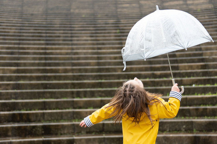 Woman with umbrella standing in rain