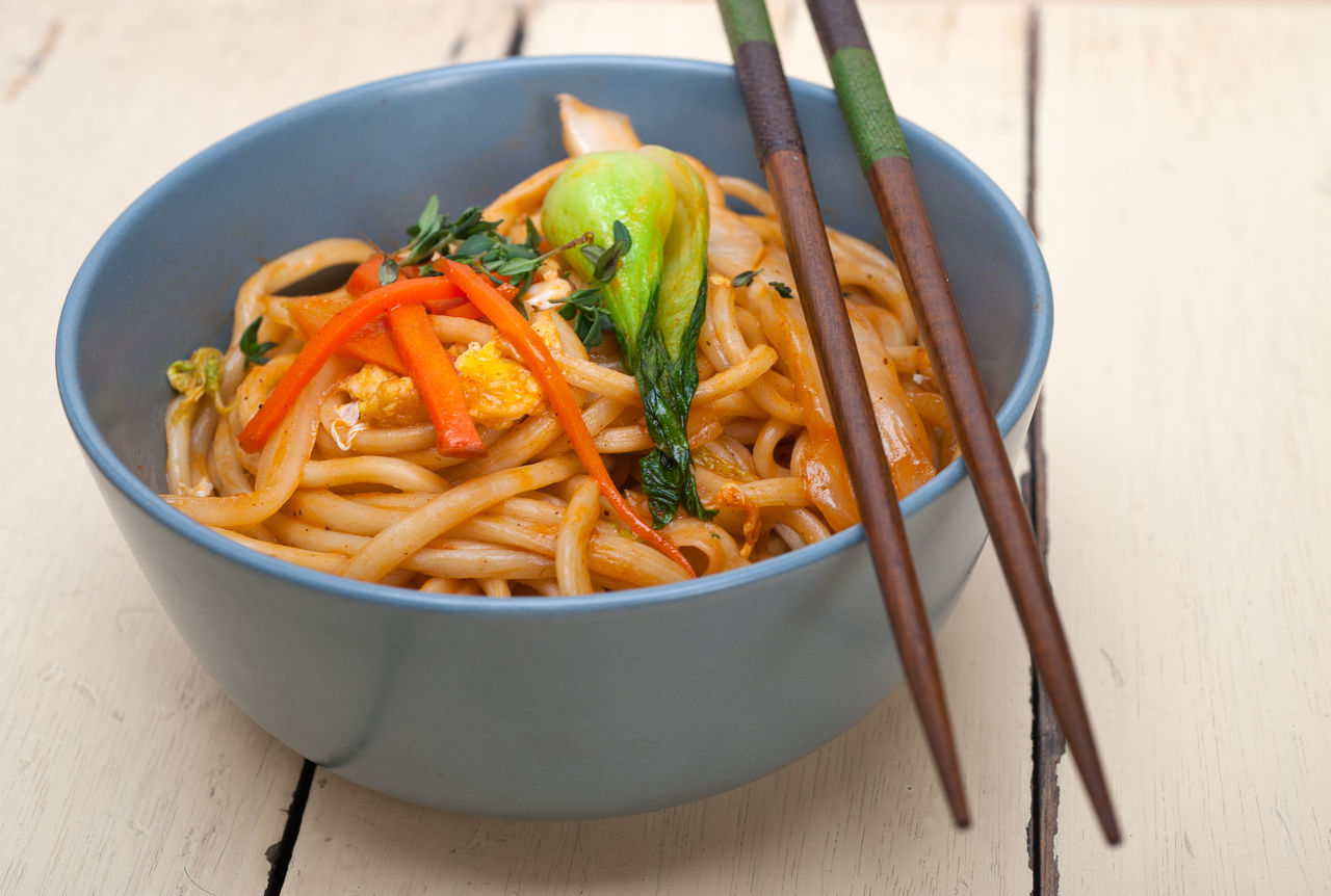 Close-Up Of Food In Bowl With Chopsticks On Table