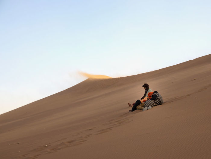 People riding in desert against clear sky