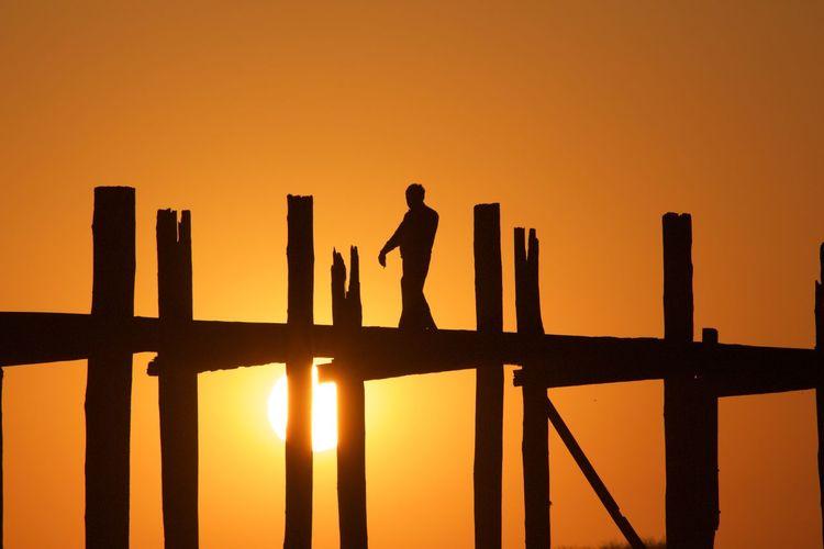 Silhouette man on bridge