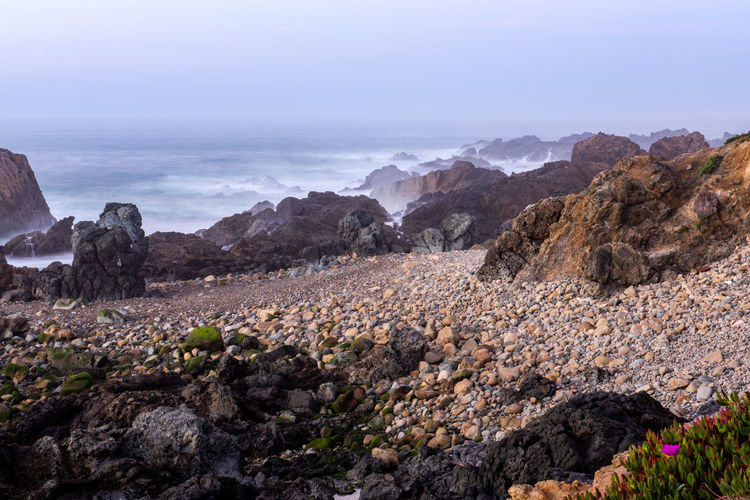 Scenic view of rocky shore and sea against sky