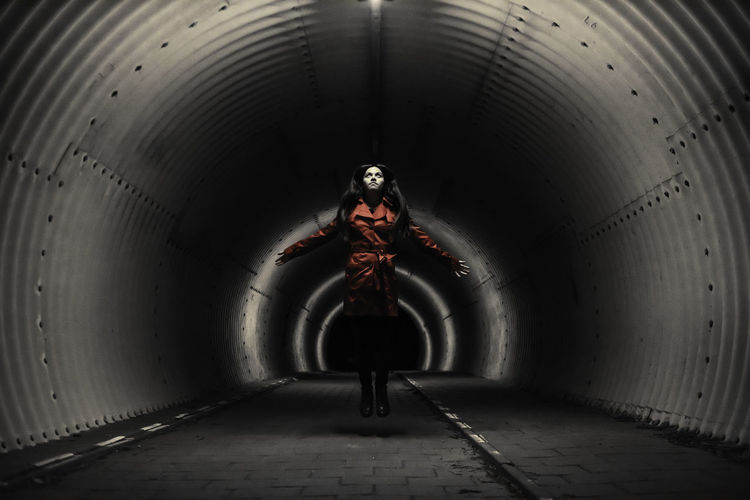 Woman standing in tunnel