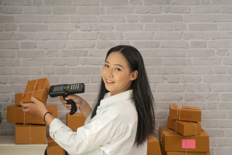 Portrait of businesswoman smiling while using bar code reader on box in office