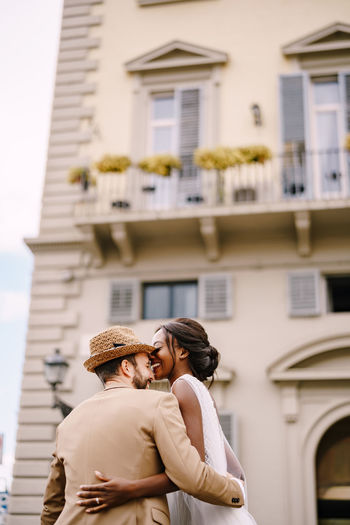Couple embracing against building in city