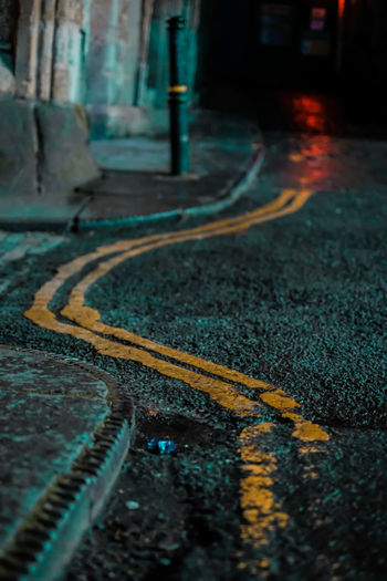 High angle view of double yellow lines on road at night