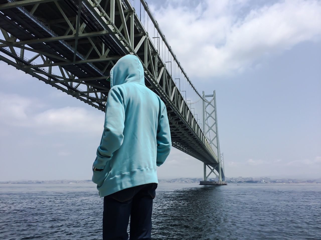 Rear view of person standing against bridge over river