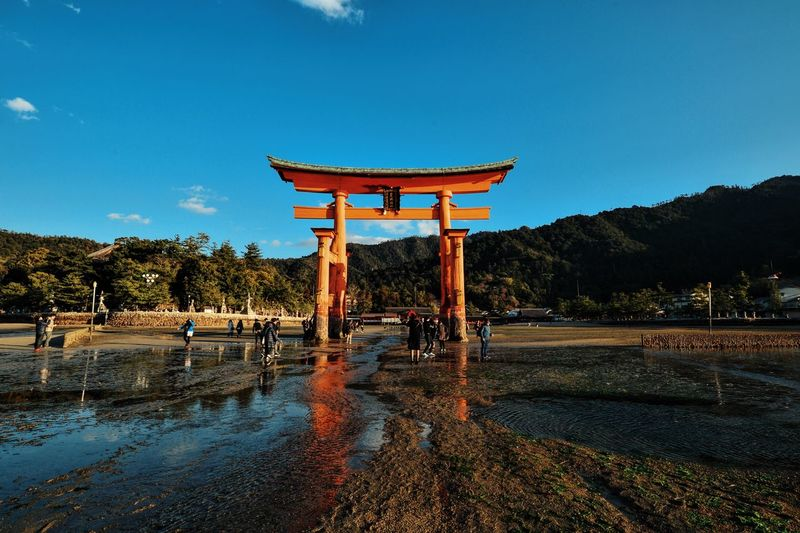 People By Torii Gate On Shore At Itsukushima Shrine Against Sky