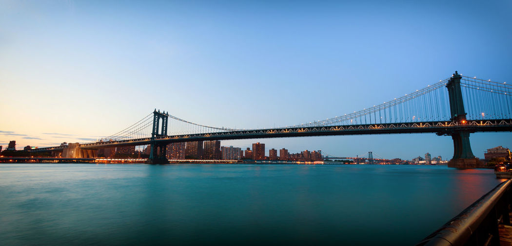 Low angle view of manhattan bridge over river against clear sky during sunset