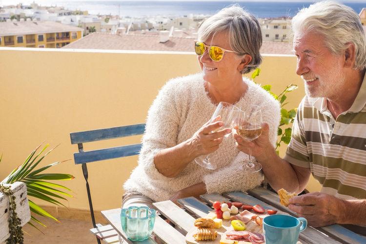 Senior Couple Toasting Drinks While Sitting In Balcony