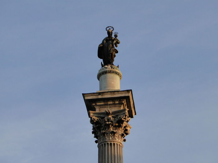 Low angle view of statue on monument against sky