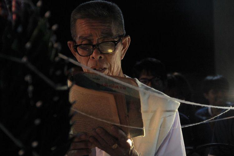 Portrait of a man holding eyeglasses