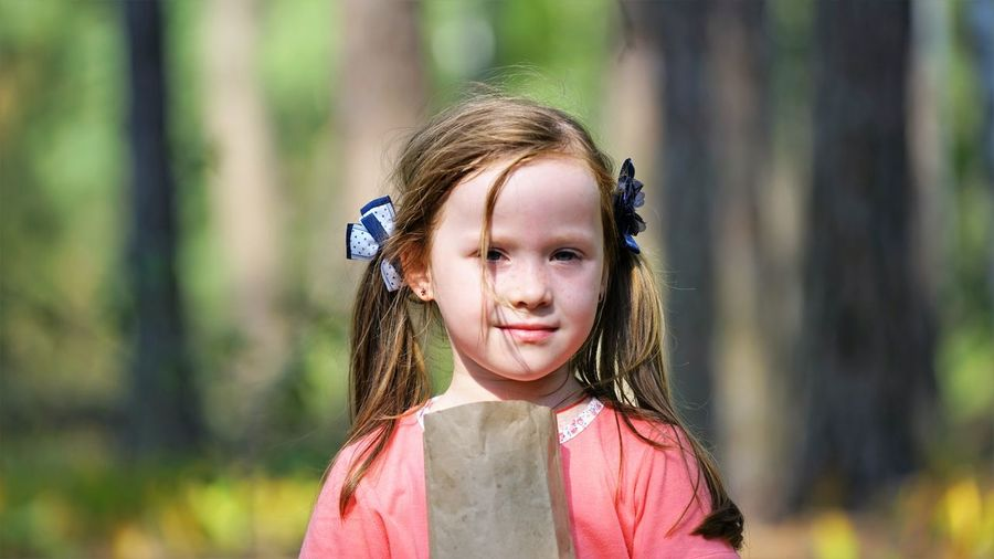 Close-up portrait of girl with paper bag against trees in forest