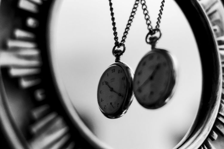 Close-up of pocket watch with reflection on mirror