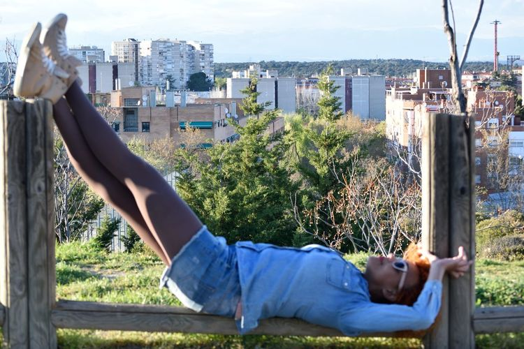 Low section of man lying down by buildings in city