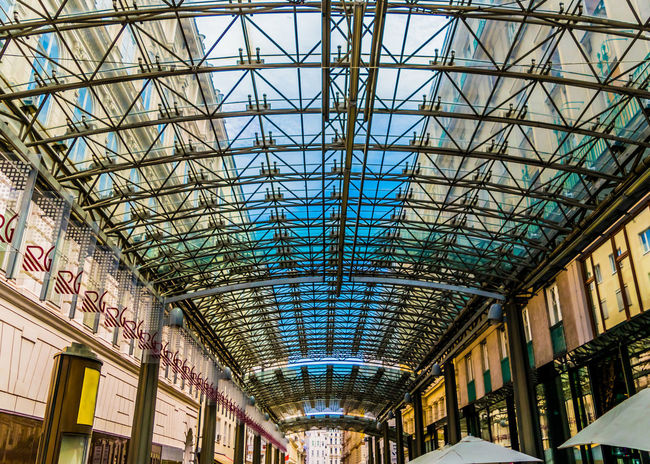 Modern architecture detail, steel and glass ceiling. Patterned glass ceiling covers gallery between older buildings. Ceiling High Roof Architecture Background Between Blue Buildings Ceiling Covers Day Design Detail Gallery Glass Inside Interior Metal Modern Older  Patterned Sky Steel Transparent Window
