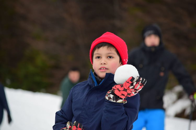 Smiling Boy Holding Snowball While Standing Outdoors