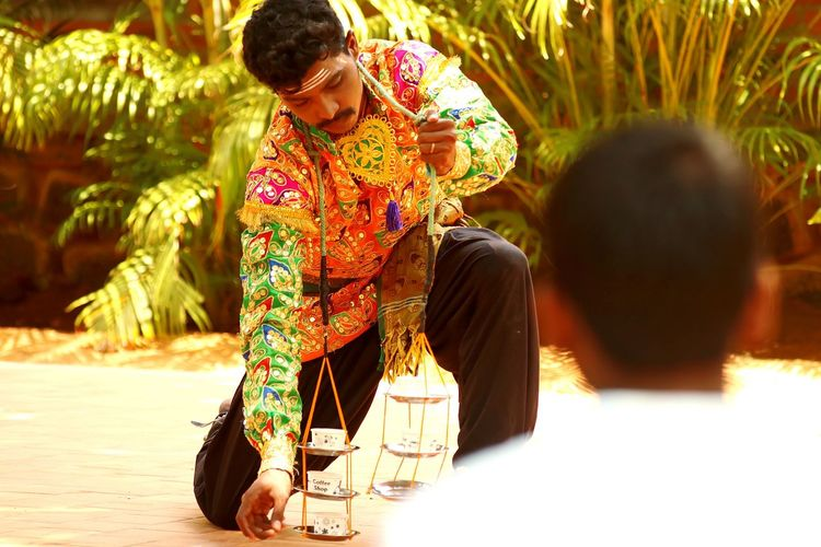 Rear view of man looking at artist performing in traditional clothing against plants