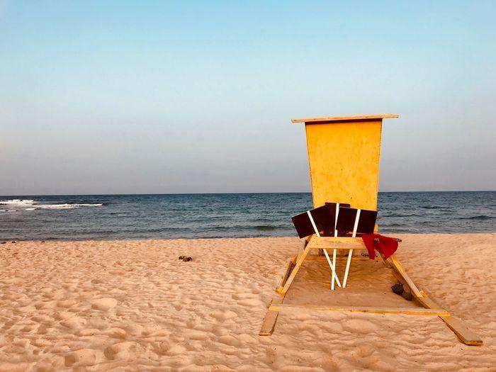 Lifeguard chair at beach against clear sky