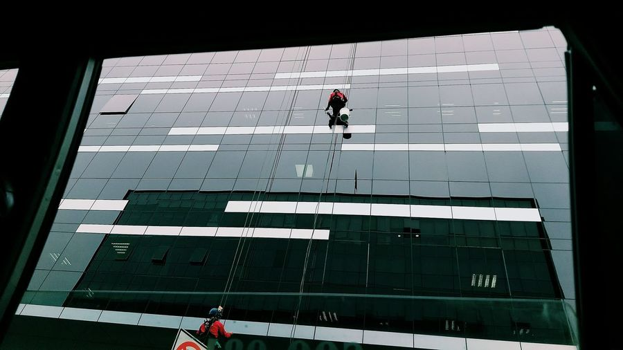 Low angle view of people working on glass building