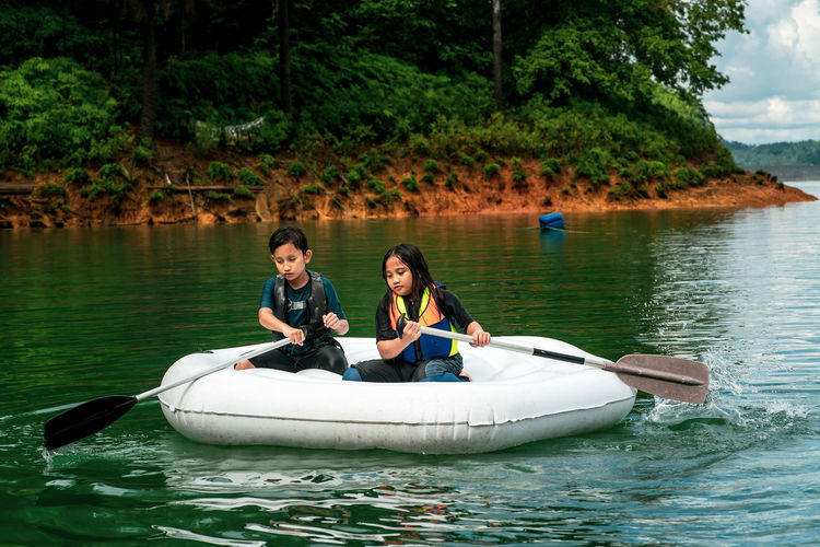 Children wearing life jackets paddling on an inflatable boat in kenyir lake, malaysia.