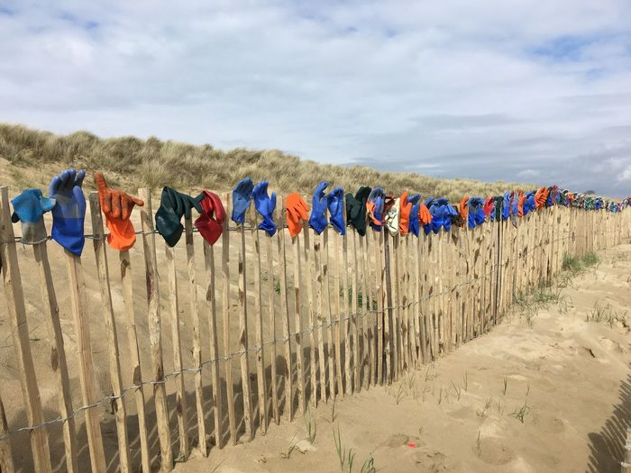 Plastic gloves all in a row!! Sky Cloud - Sky Multi Colored Nature Side By Side Beach Sand In A Row Hanging Clothing Large Group Of Objects No People Outdoors Drying