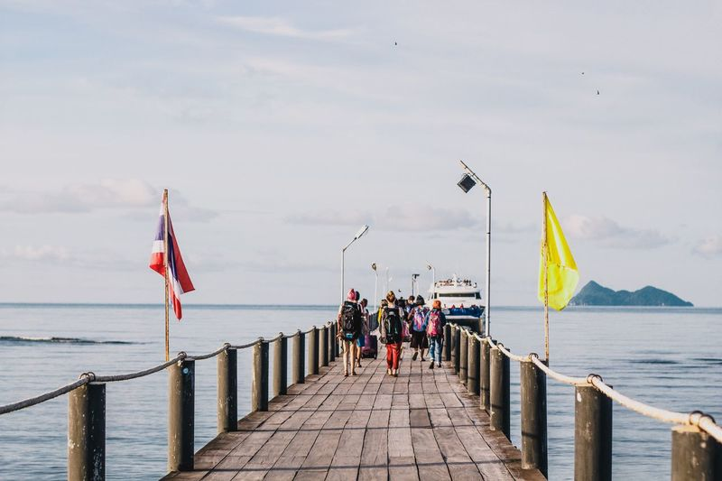 Rear view of people walking on pier over sea against sky