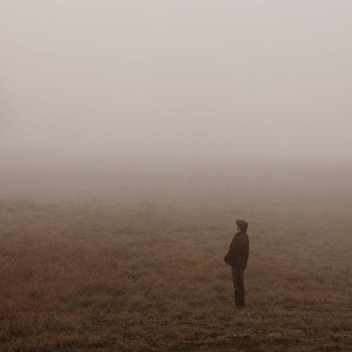 Man standing on field amidst fog