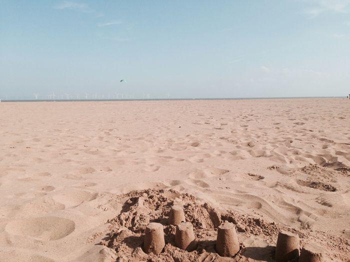 Sand castles on shore against sky