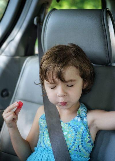 Cute girl eating candy in car