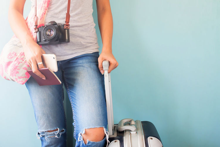 Midsection of woman with luggage standing against wall