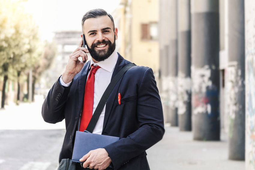 Model: Roberto Materiale Architecture Beard Business Business Person Businessman City Facial Hair Focus On Foreground Front View Happiness Males  Men Menswear Occupation One Person Outdoors Smiling Standing Well-dressed Wireless Technology Young Adult Young Men