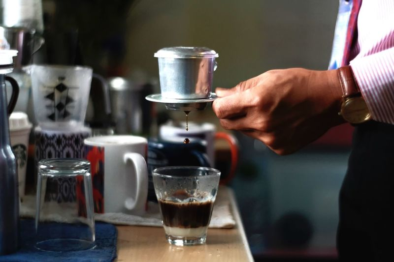 Midsection of businessman pouring coffee in cup