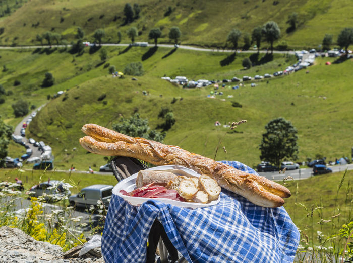 Food on folding chair against grassy landscape