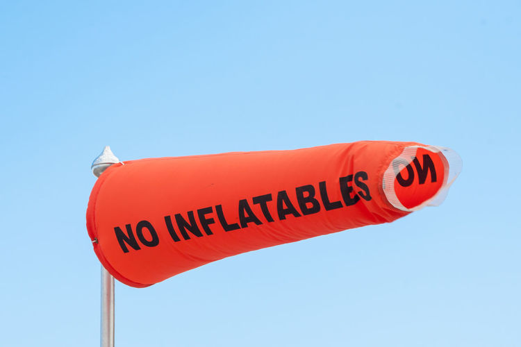 NO INFLATABLES Wind Sock Beach Blue Sky Clear Sky Close-up Communication Day Horizontal Information Sign Lincolnshire Looking Up Low Angle View Mablethorpe No People Orange Outdoors Seaside Sign Sky Summer Text Text Warning Wind Sock Windy